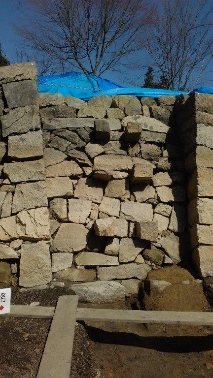 壁から突きだした石